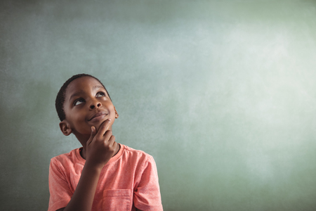 greenboard: Thoughtful boy standing against greenboard in classroom