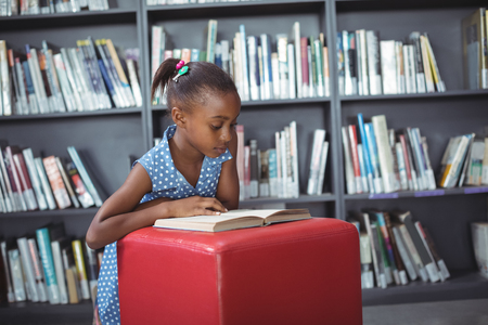 african student: Girl reading book on ottoman against bookshelf in library Stock Photo