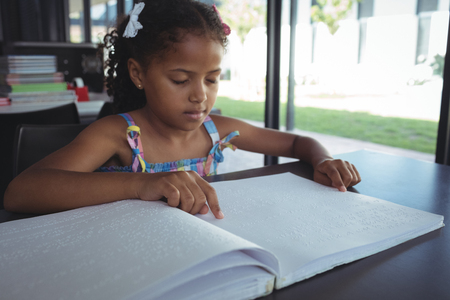 Close up of girl reading braille at desk in library