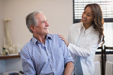 muscle retraining: Smiling female therapist looking at male patient against window at hospital ward Stock Photo