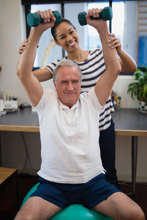 Smiling female doctor looking at senior patient lifting dumbbells in hospital ward