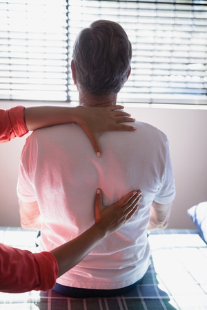 Rear view of senior male patient receiving back massage from female therapist at hospital ward Stock Photo