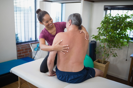 Smiling young female therapist examining back of shirtless senior male patient sitting on bed at hospital ward Stock Photo