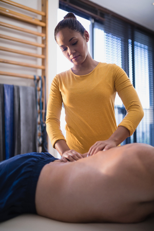 Young female therapist massaging back of senior male patient lying on bed at hospital ward Stock Photo