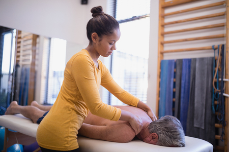Young female therapist giving neck massage to senior male patient lying on bed at hospital