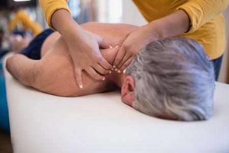 上半身裸のシニア男性患者を病棟で女性セラピストから首のマッサージを受けてベッドで横になっています。