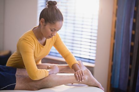 muscle retraining: Young female therapist massaging calf of male patient at hospital ward