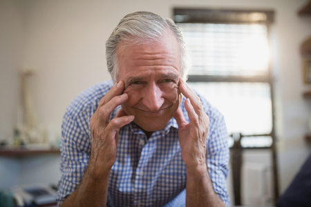 Low angle portrait of senior male patient frowning with headache at hospital ward