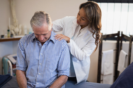 muscle retraining: Female therapist examining neck of male patient at hospital ward