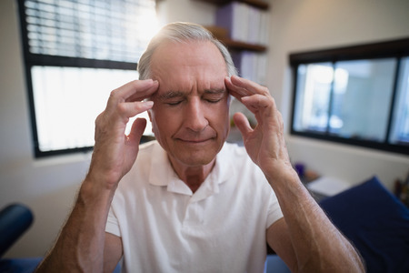 Senior male patient holding head during headache at hospital Stock Photo