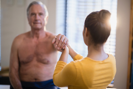 muscle retraining: Rear view of female therapist giving arm massaging to senior male patient at hospital ward