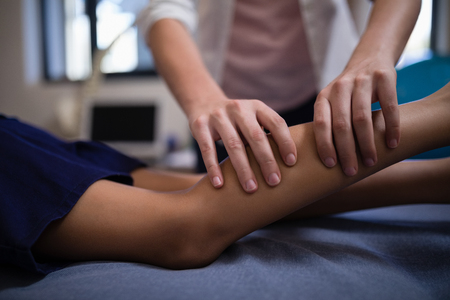 Midsection of female therapist massaging calf with boy lying on bed at hospital ward