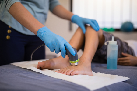 Weibliche Therapeut tragen Handschuhe scannen Füße des Jungen liegen auf Bett im Krankenhaus Station Standard-Bild - 82493098