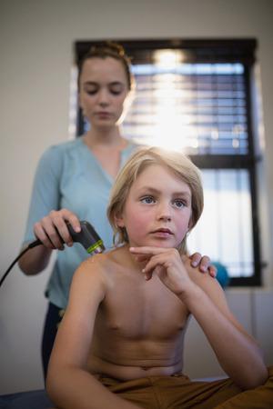 Niño sin camisa pensativo sentado con terapeuta mujer usando la máquina de ultrasonido en el hombro en la sala de hospital
