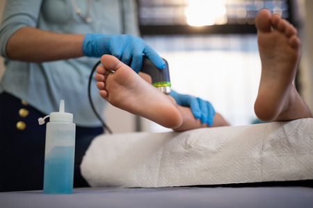 Lage sectie van jongen die echoscopie op voeten van vrouwelijke fysiotherapeut ontvangt bij het ziekenhuisafdeling