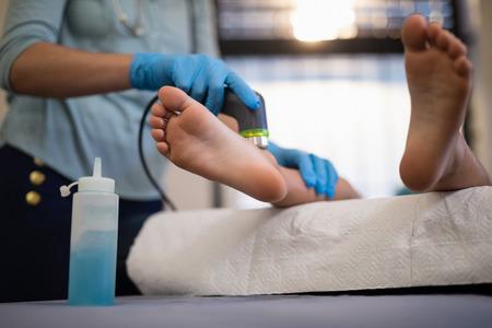 Niedriger Abschnitt des Jungen, der Ultraschalluntersuchung auf Füßen vom weiblichen Physiotherapeuten am Krankenhaus empfängt Standard-Bild - 82493233