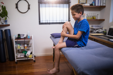 Boy frowning with knee pain while sitting on bed at hospital ward Stock Photo