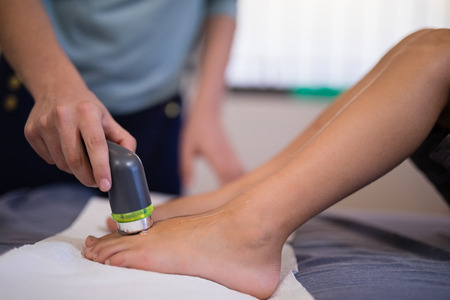 Low section of boy receiving ultrasound scan on feet from female therapist at hospital ward Stock Photo