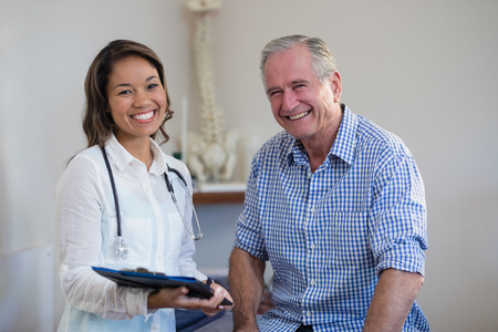 Portrait of smiling senior male patient and female therapist holding file at hospital ward Stock Photo