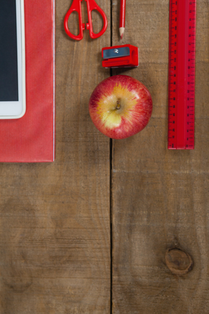back ache: Overhead view of apple, digital tablet and school supplies on wooden table
