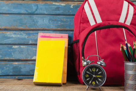 Bagpack, books, alarm clock and pen holder against blue wooden background