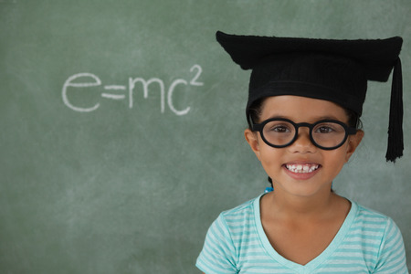 Portrait of young girl with graduation hat against chalk board