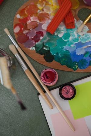 dissolve: Close-up of watercolor paints and paintbrushes on chalkboard