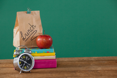 Alarm clock, lunch paper bag and apple on books stack against green background Stock Photo