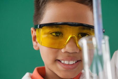 Attente schooljongen experimenteren tegen groene achtergrond