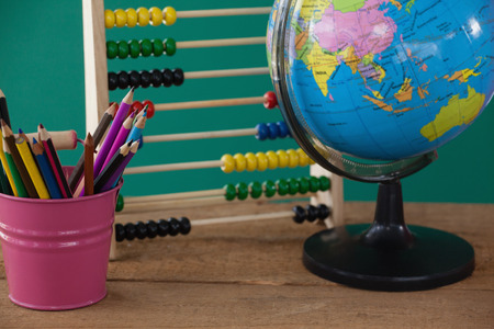Close-up of globe, penholder and abacus on wooden table Stock Photo