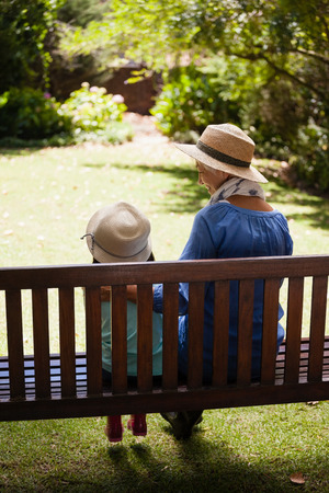 legs around: Rear view of granddaughter and grandmother wearing hats sitting on wooden bench at backyard Stock Photo