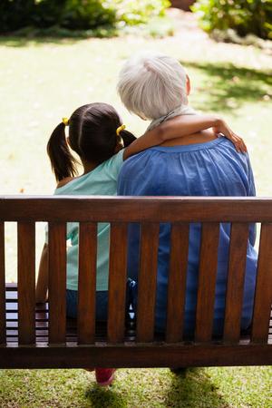 Achteraanzicht van meisje met arm rond oma zittend op houten bank op de achtertuin