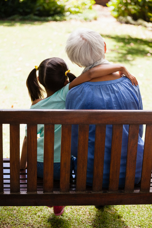 Rear view of girl with arm around grandmother sitting on wooden bench at backyard