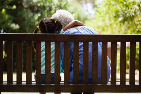 Rear view of granddaughter with arm around grandmother sitting on wooden bench at backyard