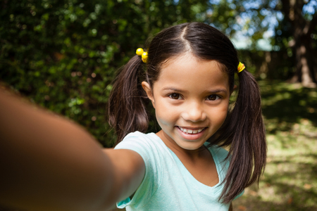 Portrait of smiling girl standing at backyard