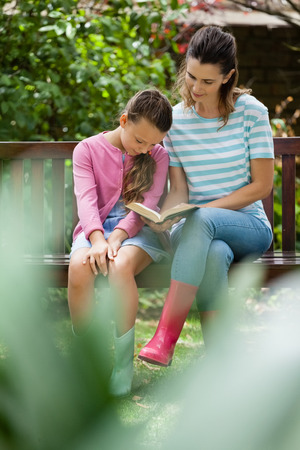legs around: Girl sitting with mother reading novel on wooden bench at backyard