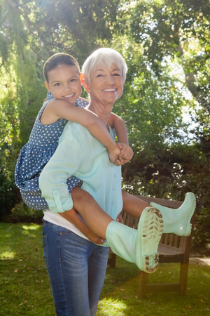 carrying: Portrait of grandmother giving piggyback ride to granddaughter against trees in backyard
