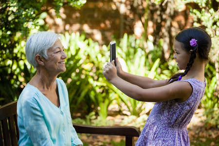 Side view of smiling girl photographing grandmother at backyard