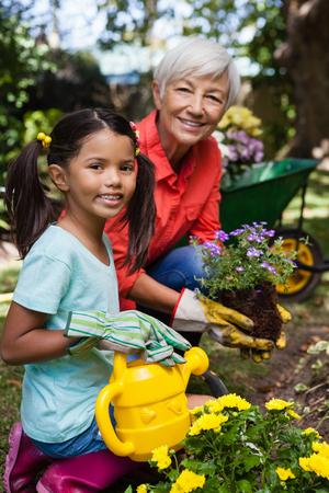 Portrait of smiling senior woman and girl watering flowers at backyard 版權商用圖片