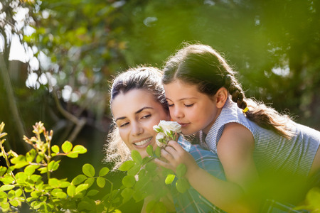 Girl smelling white roses while enjoying piggyback ride on mother in yard during sunny day
