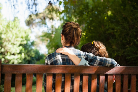 Rear view of mother and daughter sitting with arms around on wooden bench at backyard Stock Photo
