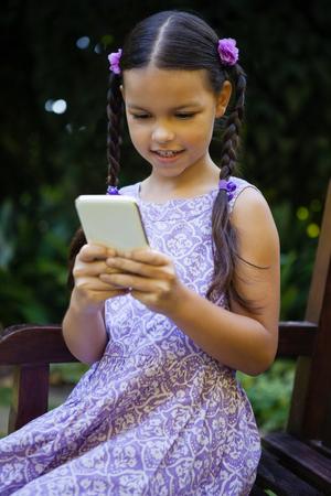 Muchacha que usa smartphone mientras que se sienta en banco en el jardín