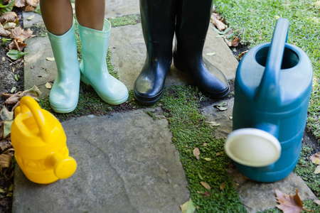 knee boots: Low section of senior woman and granddaughter standing by watering cans on walkway at backyard Stock Photo