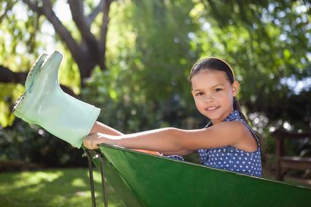 Portret van meisje die rubberlaarzen dragen die in kruiwagen bij binnenplaats zitten Stockfoto