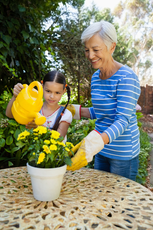 Smiling senior woman standing by granddaughter watering yellow flowers on table at backyard Foto de archivo