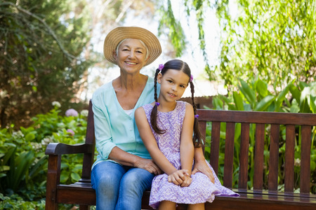 Portrait of senior woman wearing hat sitting with granddaughter on wooden bench at backyard Stock Photo