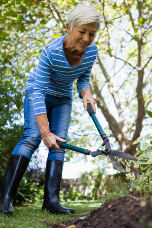 Low angle view of smiling senior woman using hedge trimmers at backyard
