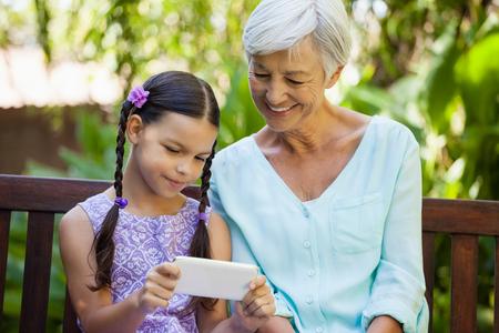 legs around: Smiling senior woman looking at girl using mobile phone at backyard