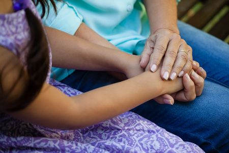 back ache: Midsection of senior woman holding hands of grandmother at backyard