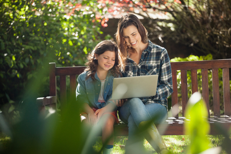 back ache: Smiling mother and daughter using laptop while sitting on wooden bench at backyard Stock Photo